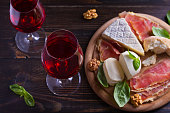 Glasses of wine with cheese, bread, nuts and jamon or prosciutto on dark wooden background. Wine and food concept. View from above, top studio shot