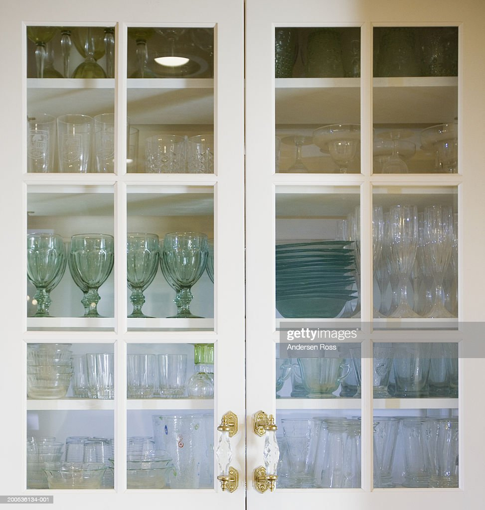 Glasses and bowls in kitchen cabinet, view through glass doors