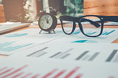 Glasses and clock on the business paper. Report chart