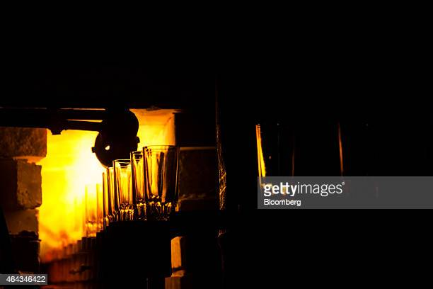 Glasses exit an annealing furnace at a Pooja Group Of Glass Industries factory in Ferozabad Uttar Pradesh India on Saturday Feb 21 2015 Prime...