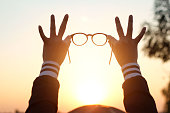 Glasses in woman hands on sunset background