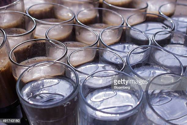 Glasses of chai and water sit at a roadside stall in Mumbai India on Friday Sept 25 2015 That sweet and milky tea concoction called chai is getting...