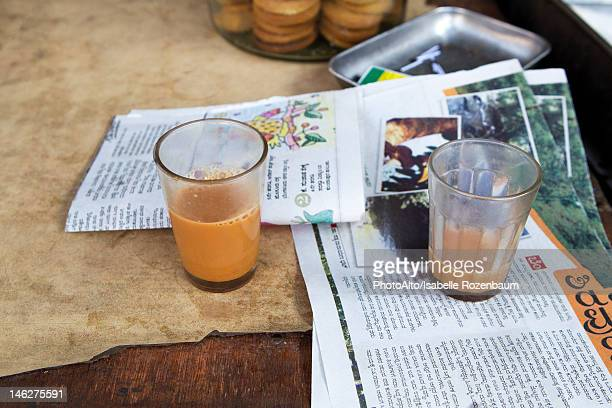 Glasses of chai tea and newspaper on table