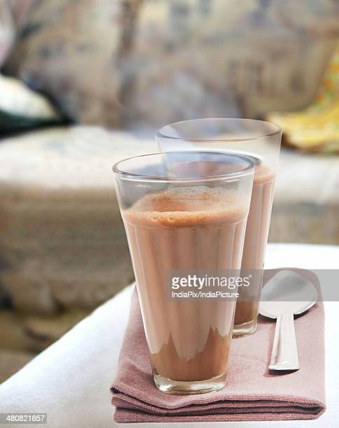 Glasses of chai with spoon on napkin