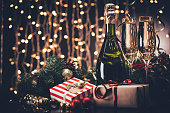 selective focus of glasses and bottle of champagne, christmas decorations and presents against festive lights