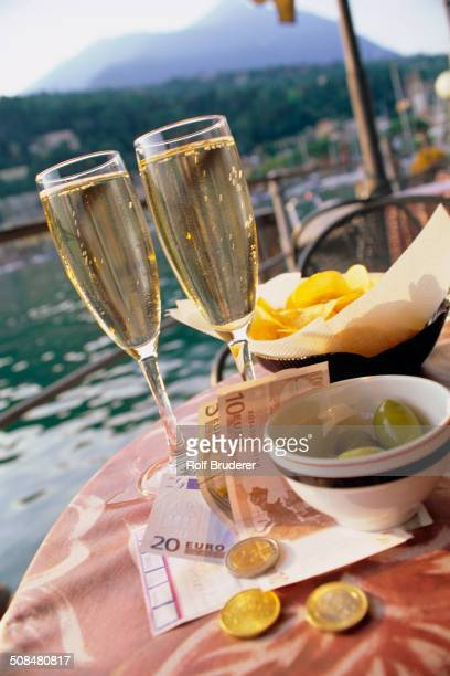 Glasses of champagne, chips, olive and money at sidewalk cafe