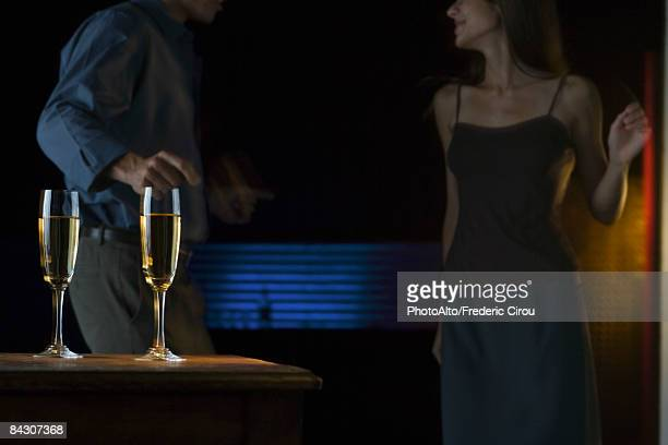 Glasses of champagne, couple dancing in darkly lit background