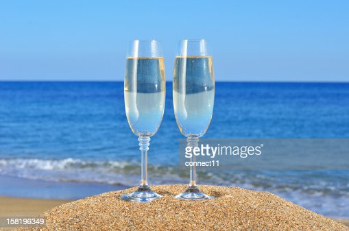 Glasses of champagne on the beach sand : Stock Photo