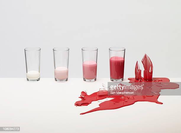 glasses of coloured liquid, one broken