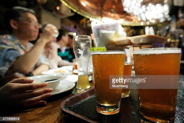Glasses of craft beer sit in a tray ready to be served inside the Bakusyu Club Popeye bar in the Ryogoku neighborhood of Tokyo Japan on Friday May 1...