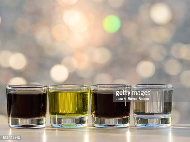 Glasses of crystal of chupito full of different alcoholic drinks of different colors , illuminated by the light of the Sun