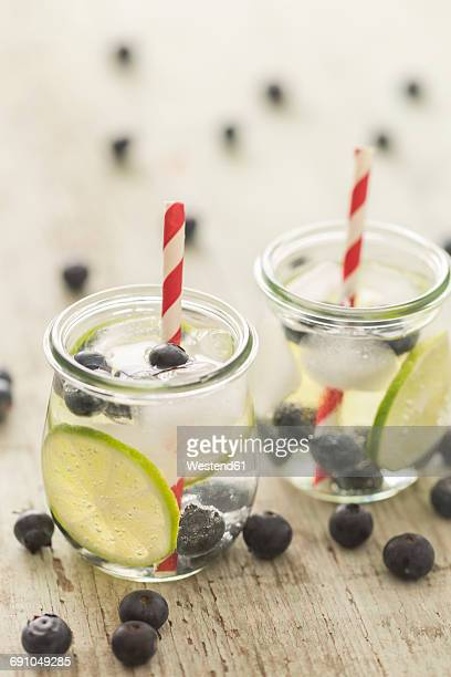 Glasses of infused water with lime, blueberries and ice cubes