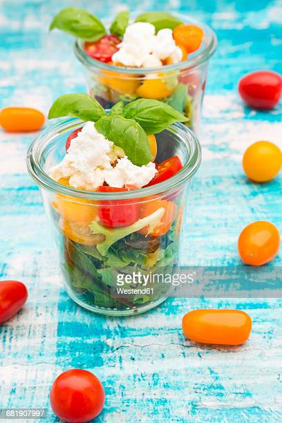 Glasses of leaf salad with goat cream cheese and tomatoes