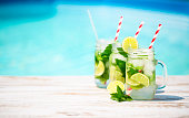 Glasses of lime lemonade near pool. Summer pool party