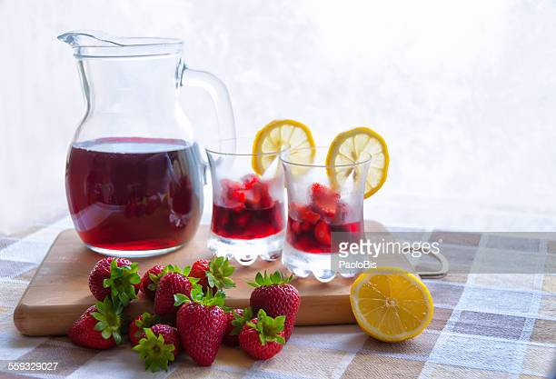 Glasses of strawberries in red wine on the table