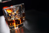 Two glasses of whiskey with ice cubes, and bottle in background, on the bar. Glasses reflected on the surface of the bar. Focus on front glass and blurred dark background. Close-up photography. Horizo