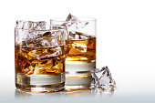 Two glasses of scotch whiskey with ice cubes, background fades to white, copy space