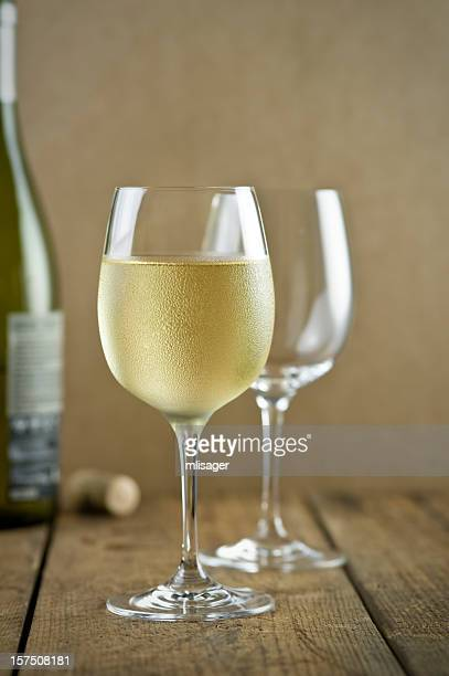 Glasses of white wine, bottle, cork on table