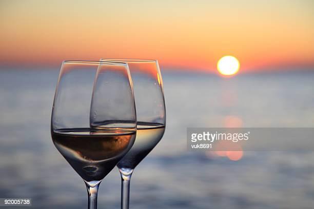 Bicchieri di vino rosso al tramonto contro