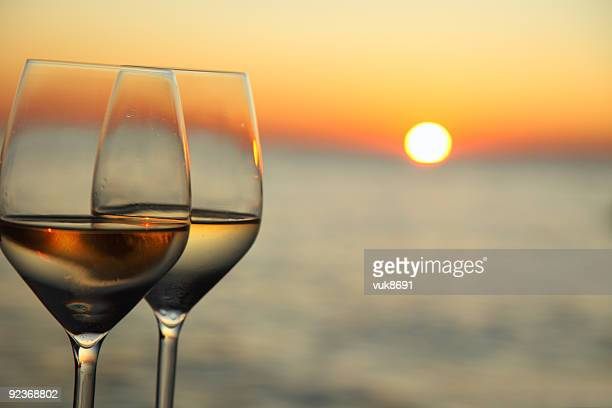 Glasses of wine against red sunset