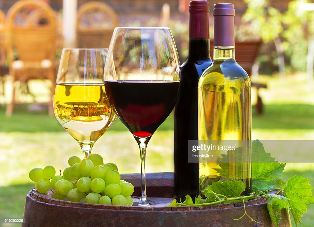 Glasses of wine on old barrel in a garden : Stock Photo