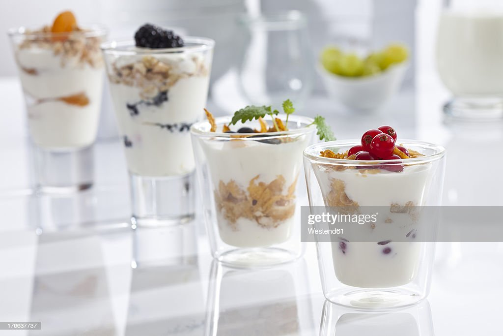 Glasses of yogurt with muesli, cornflakes and fruits on white background, close up