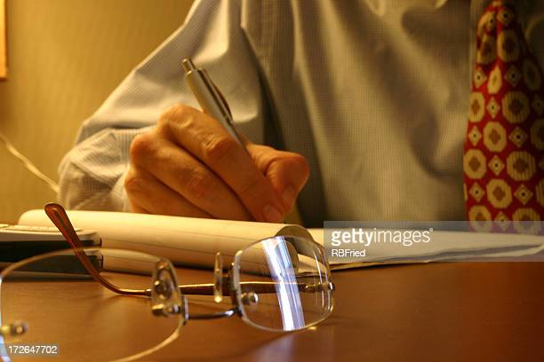 Glasses on a desk next to mans hand writing on a notepad