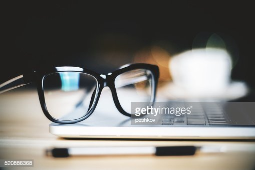 Glasses on laptop with pen, close up : Stock Photo