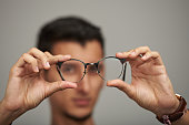 Glasses on man hands close up in blurred background