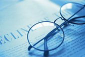 Glasses on newspaper, high angle view, close up, toned image