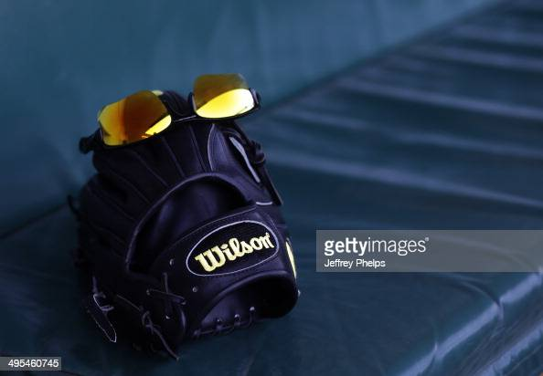 Glasses reflect the sun on a Wilson glove in the dugout in Wrigley Field before the Chicago Cubs and New York Mets baseball game on June 3 2014 in...