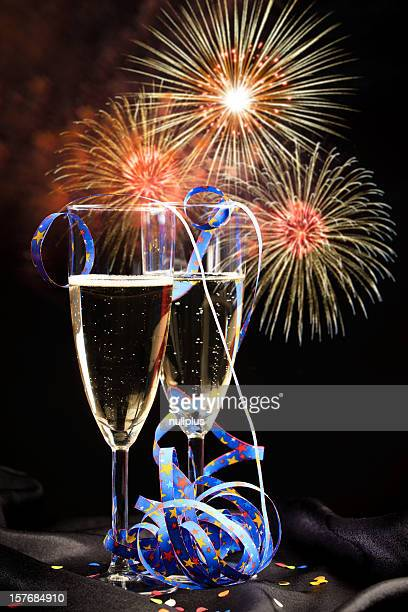 glasses with champagne and fireworks in the background