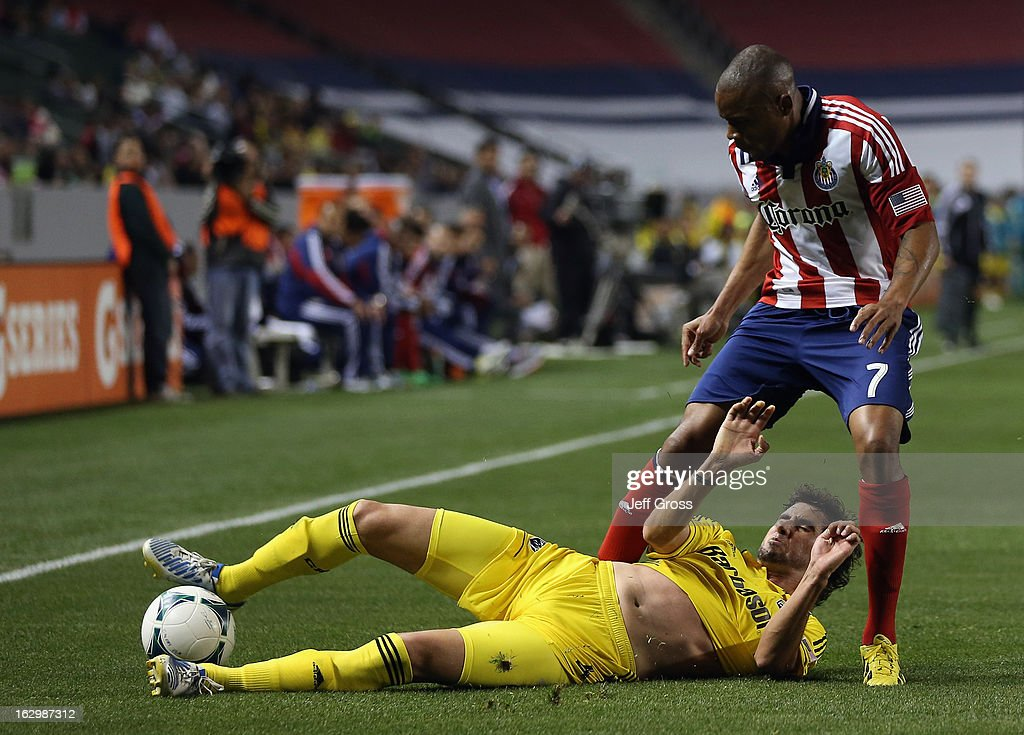Glauber #4 of Columbus Crew tackles the ball away from Tristan Bowen #7 of Chivas USA in the second half at The Home Depot Center on March 2, 2013 in Carson, California. The Crew defeated Chivas USA