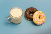 Glazed donuts and milk in a glass cup on a blue background
