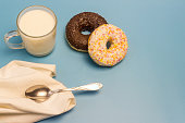 Glazed donuts, milk in a glass cup, a small spoon and a napkin on a blue background