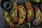 grilled glazed eggplants on black background, top view