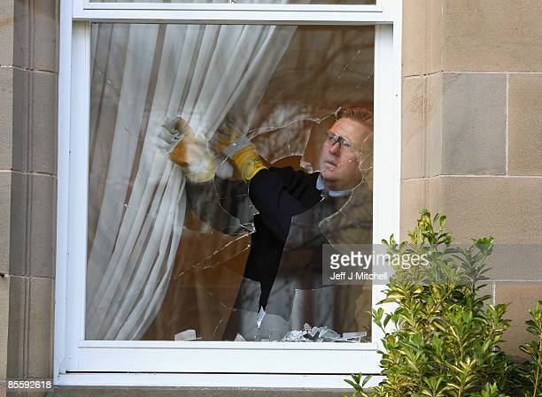 A glazier prepares to remove a smashed window at the Edinburgh home of former Royal Bank of Scotland boss Sir Fred Goodwin after it was attack by...