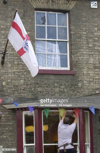 A glazier replaces shattered windows of the Red Lion in Thetford Norfolk where local Portuguese fans watched Thursday night's Euro 2004 quarterfinal...