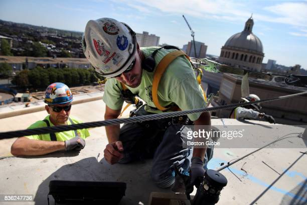 Glaziers Gary DiBella left and Kyle Segee right of Metro Glass Metal install anchors for the glass curtain wall on the ninth floor of One Dalton...