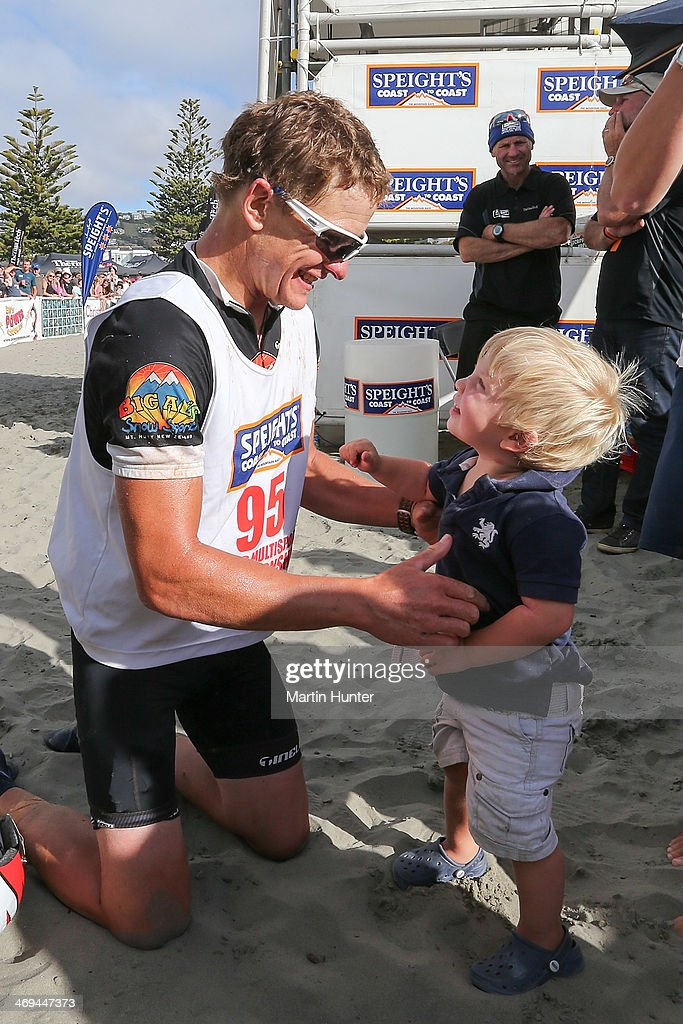 Glen Currie of Wanaka celebrates with his son after finishing the one day individual event during the Speights Coast to Coast on February 15, 2014 in Christchurch, New Zealand.