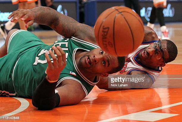 Glen Davis of the Boston Celtics and Amar'e Stoudemire of the New York Knicks reach for the ball as he bounces out of bounds in the first quarter of...