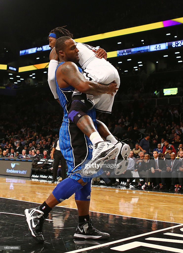 Glen Davis #11 of the Orlando Magic catches Gerald Wallace #45 of the Brooklyn Nets in his arms after Wallace scored during their game at the Barclays Center on January 28, 2013 in the Brooklyn borough of New York City.