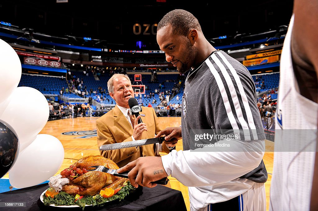 Glen Davis #11 of the Orlando Magic cuts a Thanksgiving turkey following his team's game against the Detroit Pistons on November 21, 2012 at Amway Center in Orlando, Florida.