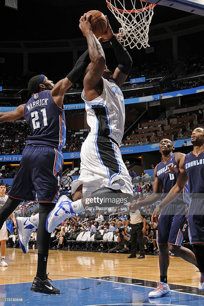 Glen Davis #11 of the Orlando Magic drives to the basket against Hakim Warrick #21 of the Charlotte Bobcats during a game on January 18, 2013 at Amway Center in Orlando, Florida.
