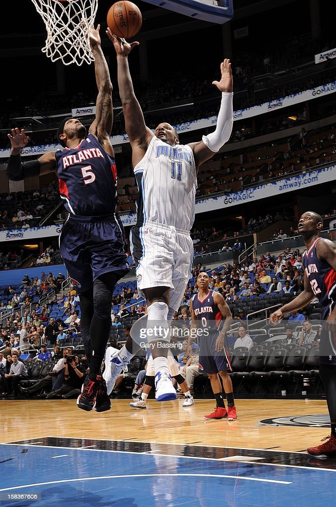 Glen Davis #11 of the Orlando Magic drives to the basket against Josh Smith #5 of the Atlanta Hawks on December 12, 2012 at Amway Center in Orlando, Florida.