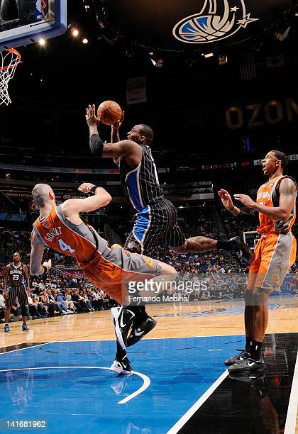 Glen Davis of the Orlando Magic knocks over Marcin Gortat of the Phoenix Suns and he drives to the basket during the game on March 21 2012 at Amway...