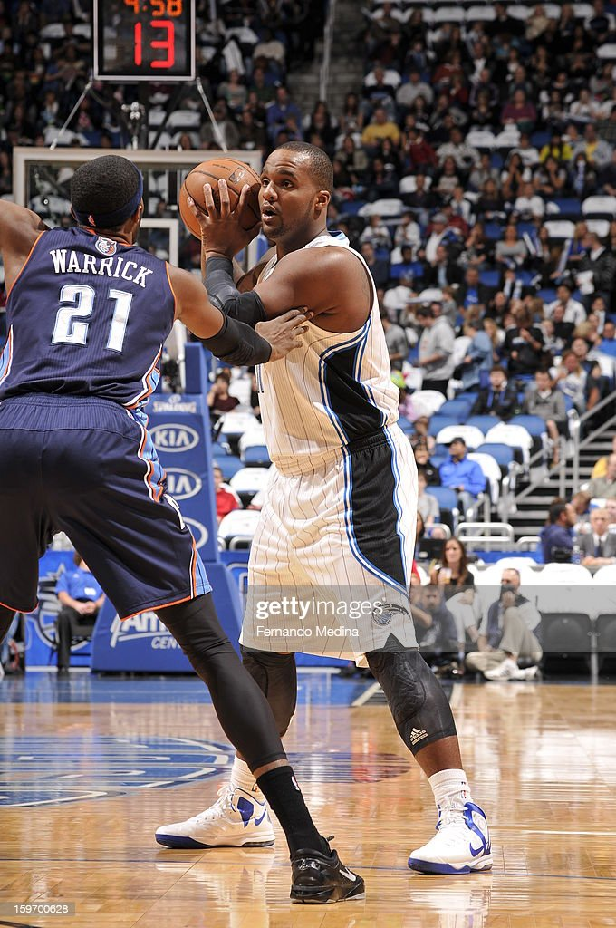 Glen Davis #11 of the Orlando Magic looks to pass the ball against Hakim Warrick #21 of the Charlotte Bobcats on January 18, 2013 at Amway Center in Orlando, Florida.