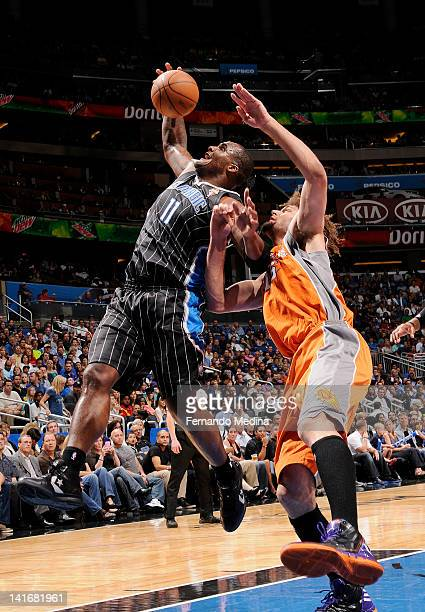Glen Davis of the Orlando Magic reaches for the ball against Robin Lopez of the Phoenix Suns during the game on March 21 2012 at Amway Center in...