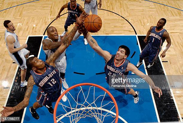Glen Davis of the Orlando Magic reaches for the ball against Tyrus Thomas and Byron Mullens of the Charlotte Bobcats during the game on January 17...