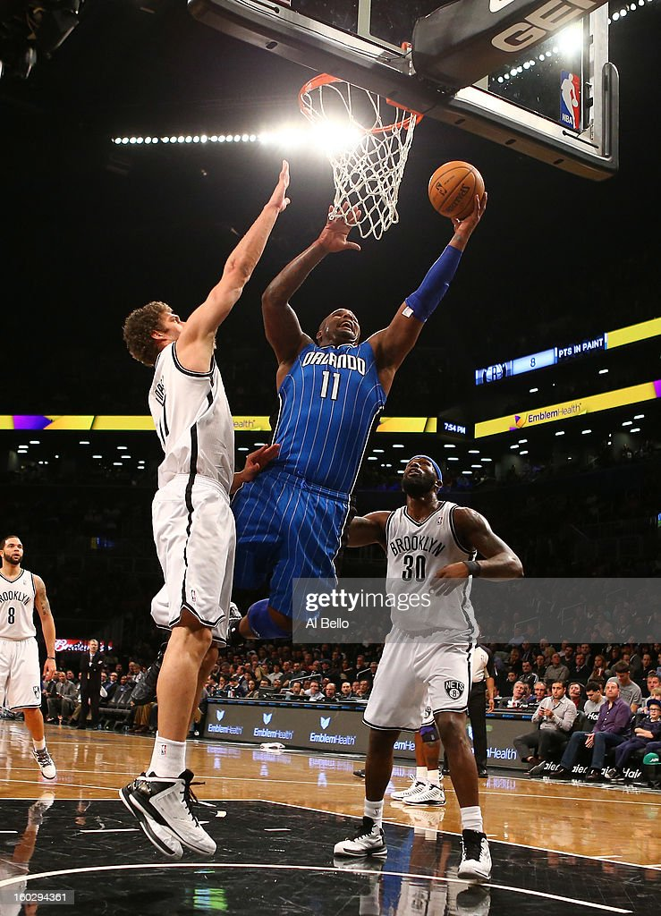 Glen Davis #11 of the Orlando Magic scores against Brook Lopez #11, and Reggie Evans #30 of the Brooklyn Nets during their game at the Barclays Center on January 28, 2013 in the Brooklyn borough of New York City.